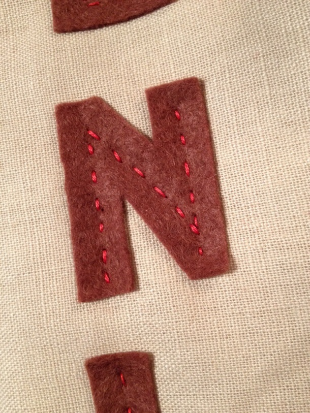 and some letters cut out of felt hand stitched with red embroidery thread.